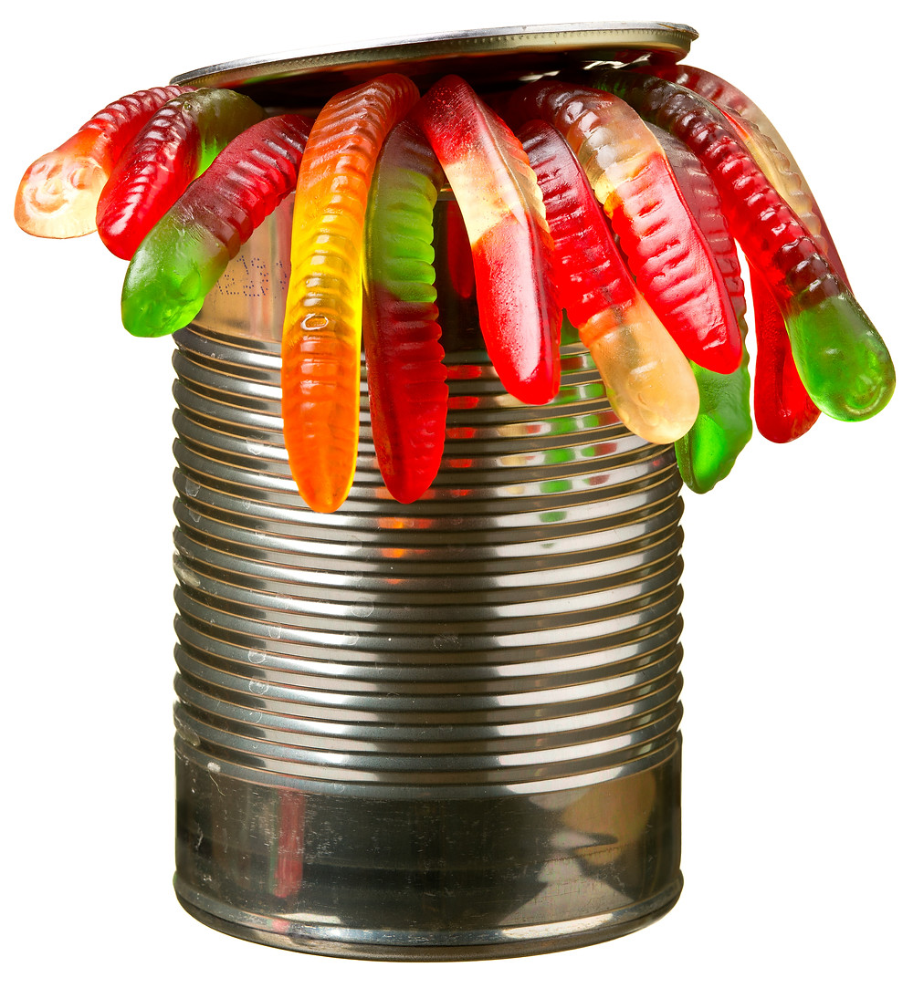 A tin can with multi-coloured jelly sweets in the shape of worms oozing out of the top