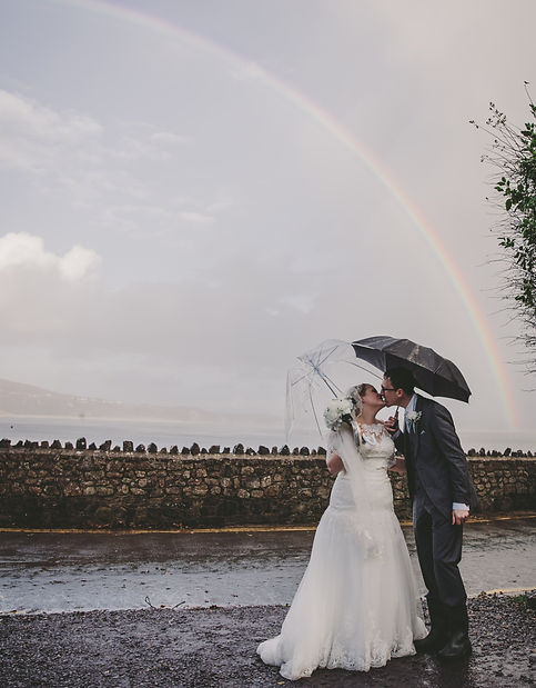 A couple kissing under umbrellas in the rain with a beautiful rainbow behind them