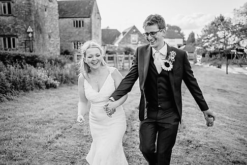 A couple holding hands and laughing in a rural village