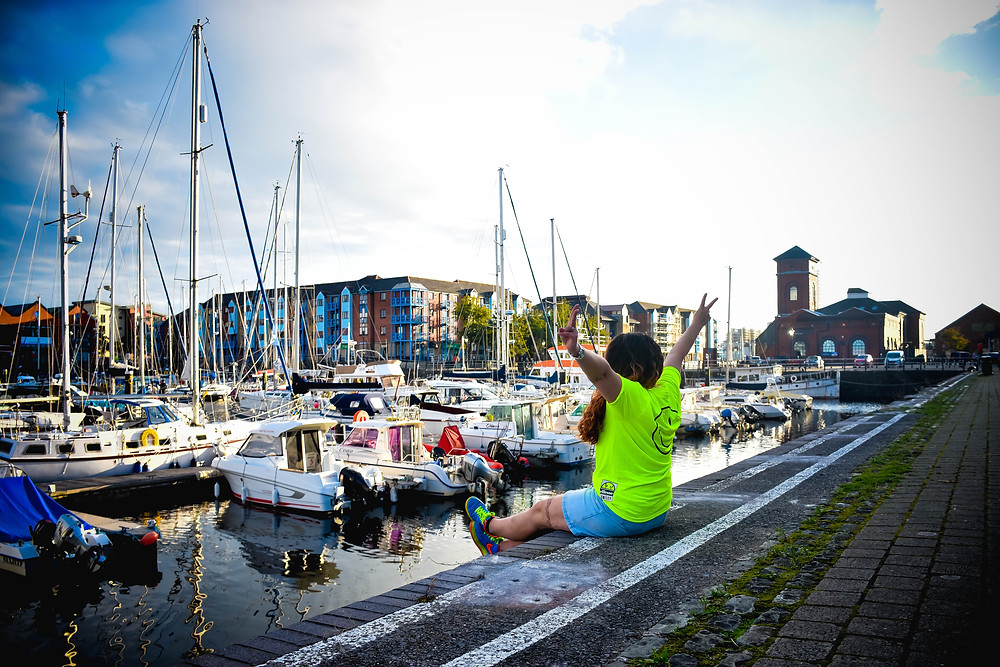 A photograph of Sian sat with her legs dangling over the water at Swansea Marina. There are lots of yachts in the background. Sian has her hands up in the air, making peace signs with her fingers. She is wearing an illuminous t-shirt and bright blue trainers