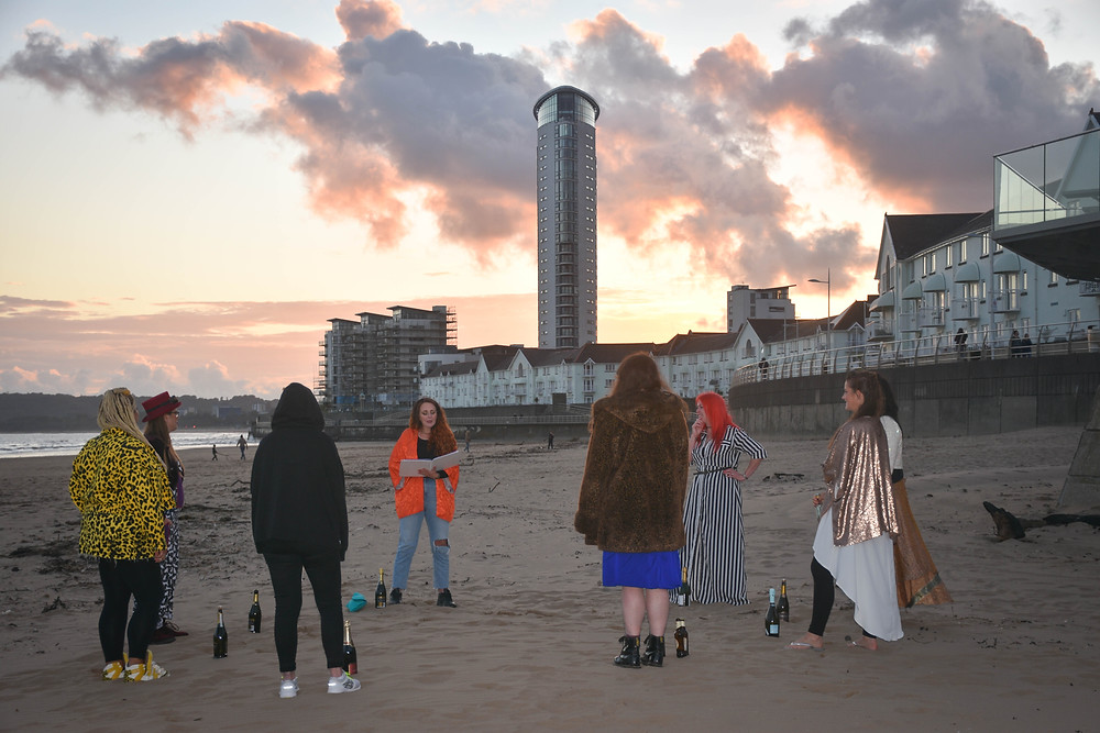 Sian and seven friends, standing in a circle on Swansea Bay as she begins performing a Celebration of Friendship ceremony. In the background you can see the Meridian Tower and some of the residential falts on Swansea Marina. The sun is setting and the sky is a little cloudy and the clouds are reflecting colours of pink and orange