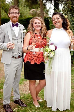 Sian Julia Jackson, wedding celebrant, standing and smiling with a happy couple holding Chamagne flutes