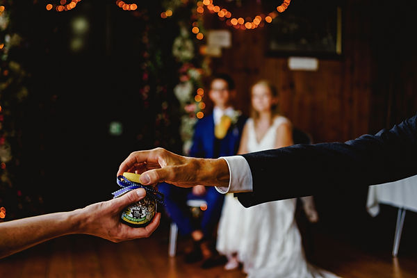 Guests at this humanist wedding ceremony were invited to take part in a ring warming ceremony which involved two wedding rings tied to a Marmite jar being passed aroung=d the wedding guests so they could send good wishes to the bride and groom