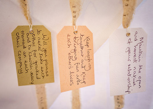 A couple's non traditional wedding vows handwritten on tags attached to handfasting ribbons