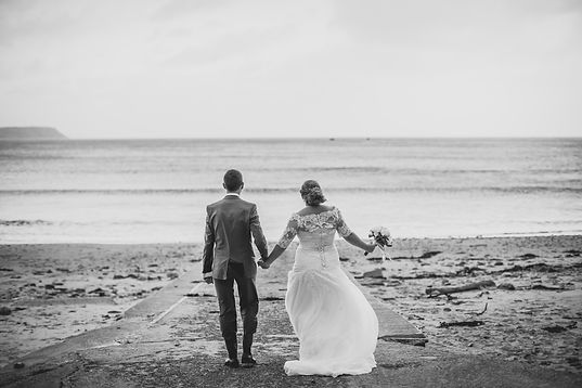 Shot of a cople from behind and they are holding hands facing the sea on Oxwich Bay on their winter wedding day