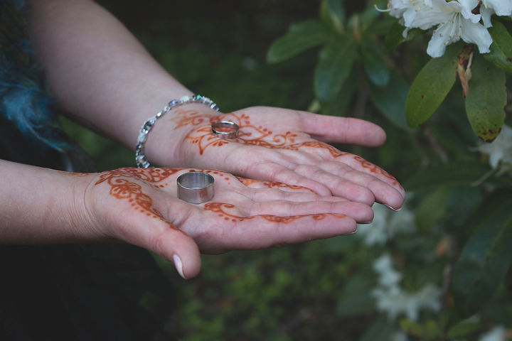 A bride with henna tattoos on her hands. She is holding two stainless steel wedding rings