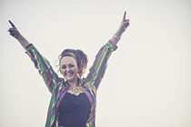 Sian Jackson simling with her arms reached up into the air wearing a stripey, colourful shirt
