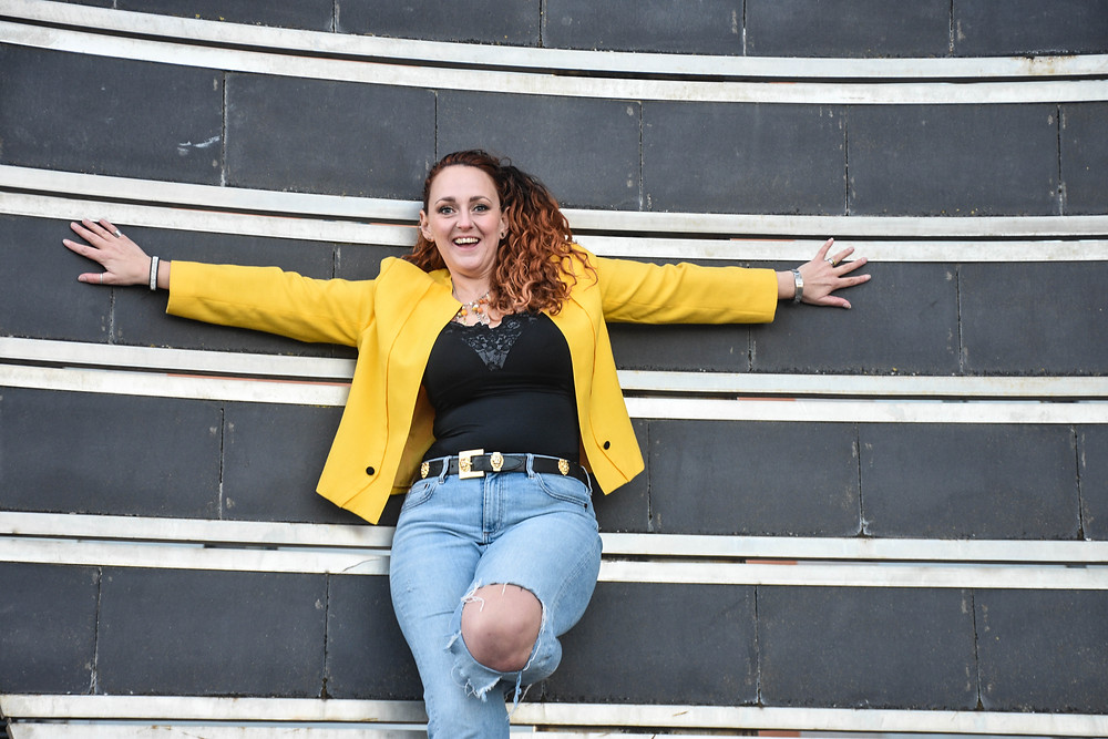 Sian Julia Jackson, Humanist Celebrant, looking very happy leaning up against a metal sculpture at Swansea Marina. She has her arms spread out wide and is wearing a  90's style, yellow jacket, ripped jeans and a black and gold belt. Her curly hair is worn in a side ponytail.hair