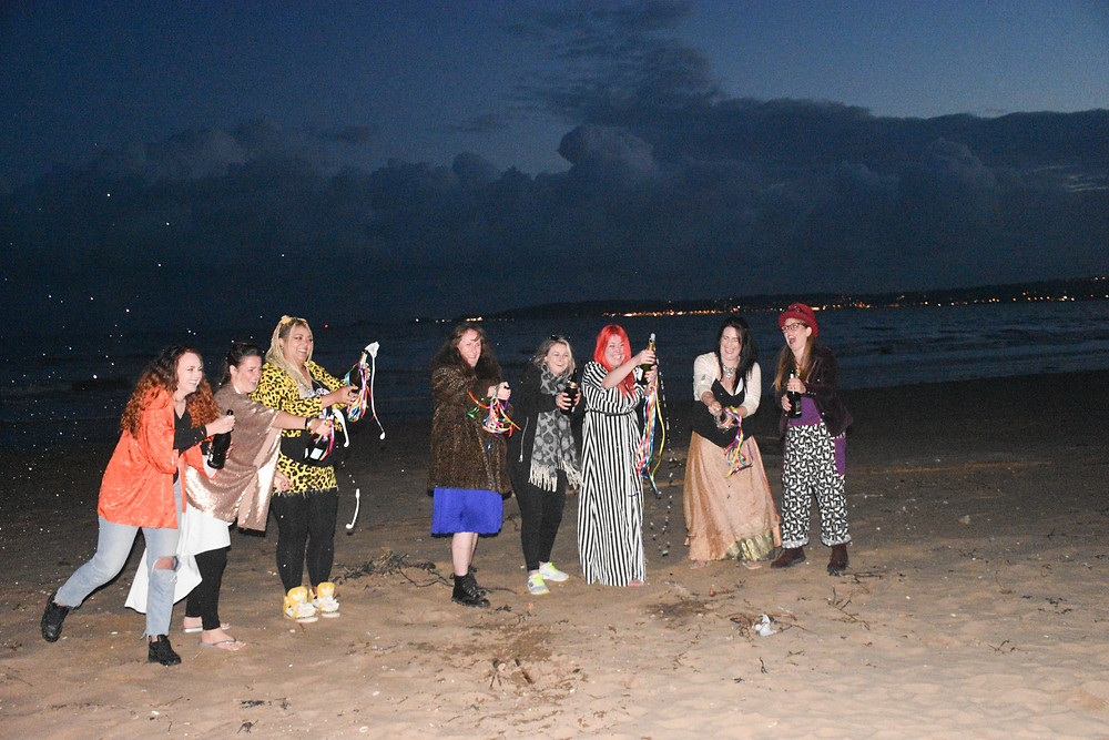 Sian and her seven friends are standing in a line, all popping bottles of fizzy wine. They are all smiling and there is foam from the bottles spraying all over the sand. It's dark and you can see the lights of Mumbles in the background