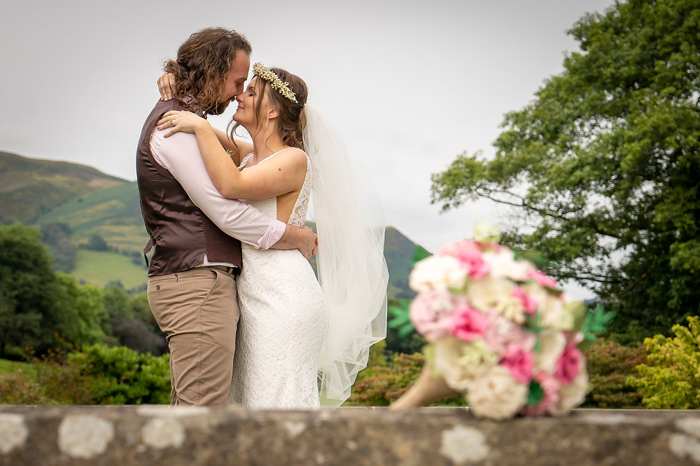 A couple embracing with mountains in the background and the bride's bouquet in the forground at Plan Dinam House