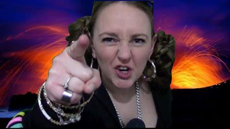 Sian Jackson in character for a performance pointing at the camera wearing lots of jewelry with an imaginary volcano eruputing in the backgroud.