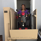 A woman riding a lift in a scooter