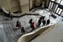 Students walk down the grand staircase at City Hall
