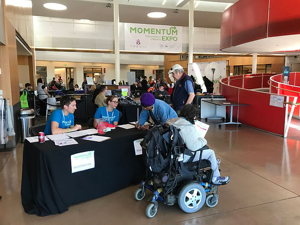 A guest in a wheelchair visit the registration table at the Momenum Expo