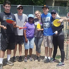 A group of people with frisbees smilin