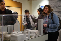 A girl smiles in front of a scale model of City Hall