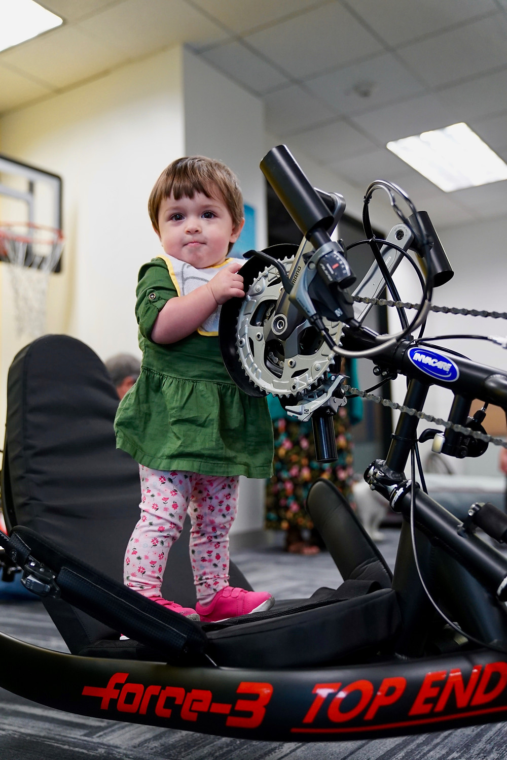 A young girl proudly stands on a handcycle