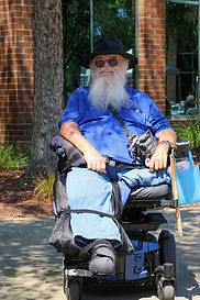 A man with a grey beard riding a scootr