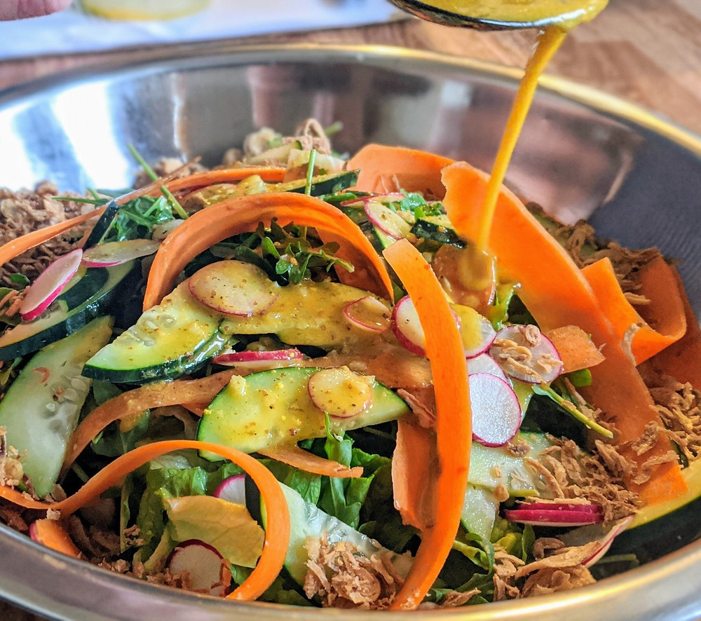 sliced vegetables in a stainless steel bowl covered in salad dressing
