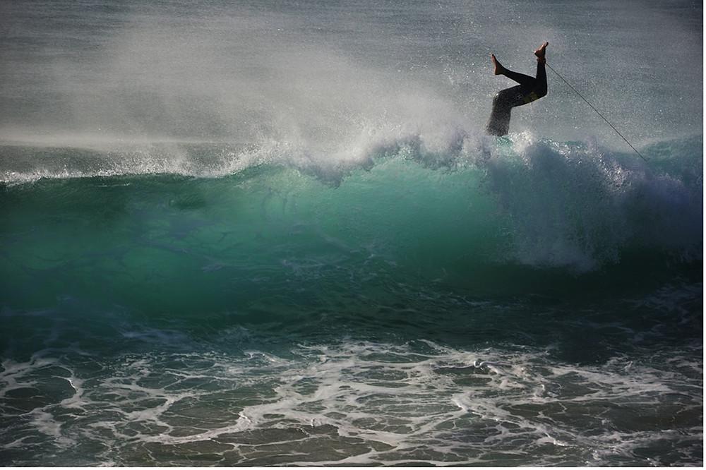 Chute d'un surfeur dans une vague bleu turquoise