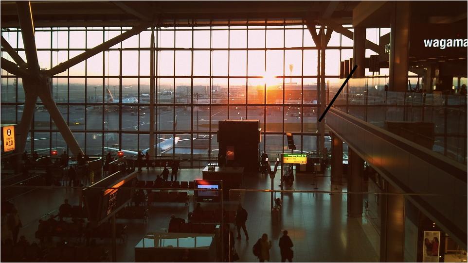 Le soleil ce couche sur la grande face vitrée de l'aéroport. Les voyageurs attendent leur avion dans ces belles couleurs.
