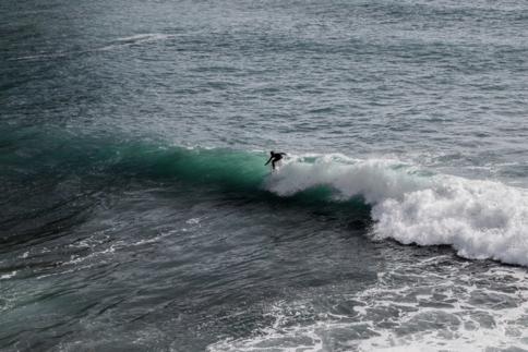 Surfeur qui surf une vague bleu turquoise du sud-est