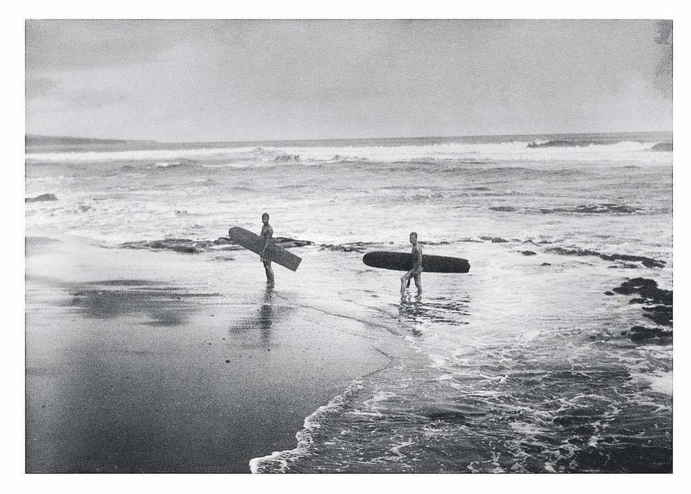 Photo noir et blanc de deux surfeur au bord de l'eau