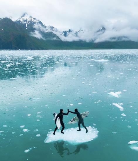 Deux surfeur sur un bout de glace en plein milieu de l'Artique