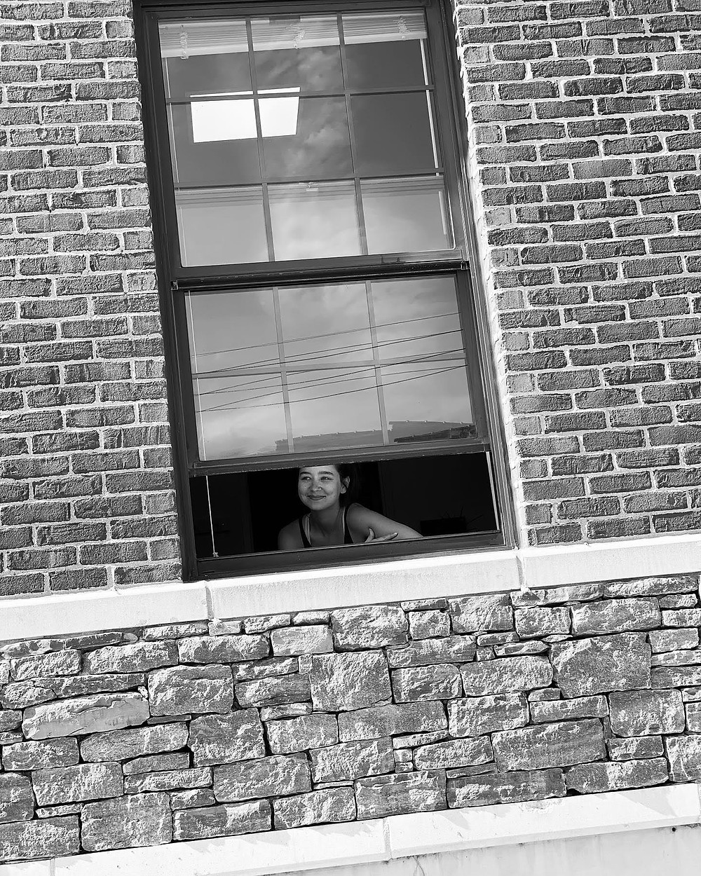 A woman is in a brink building. She looks out the open window and smiles.