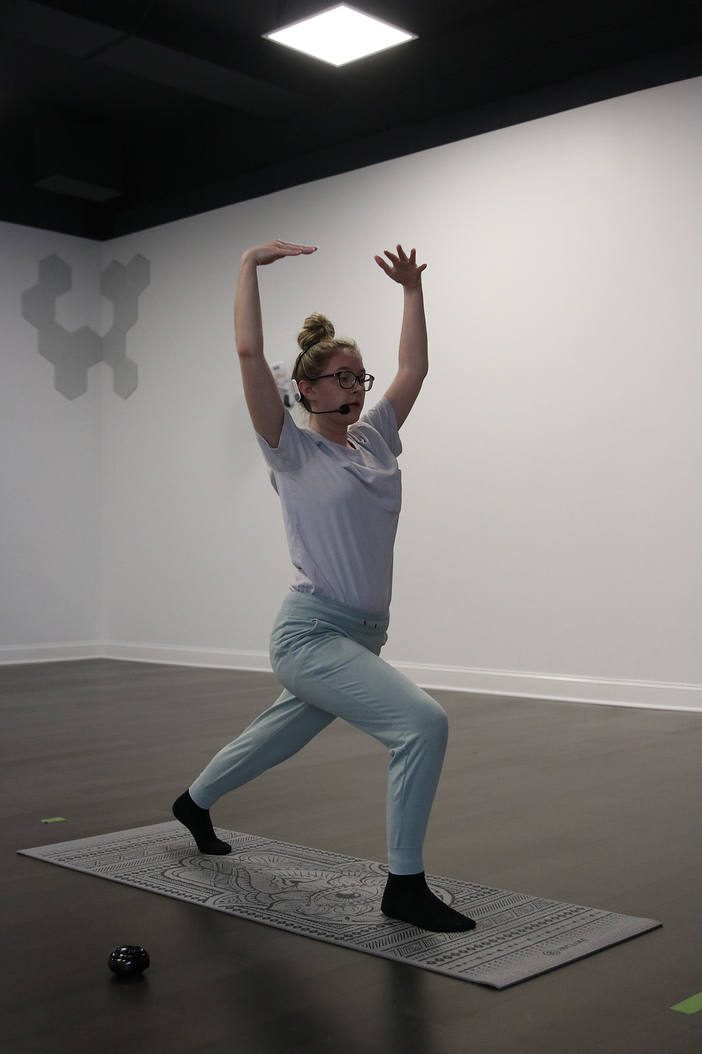 A woman completes a yoga pose in yoga studio.