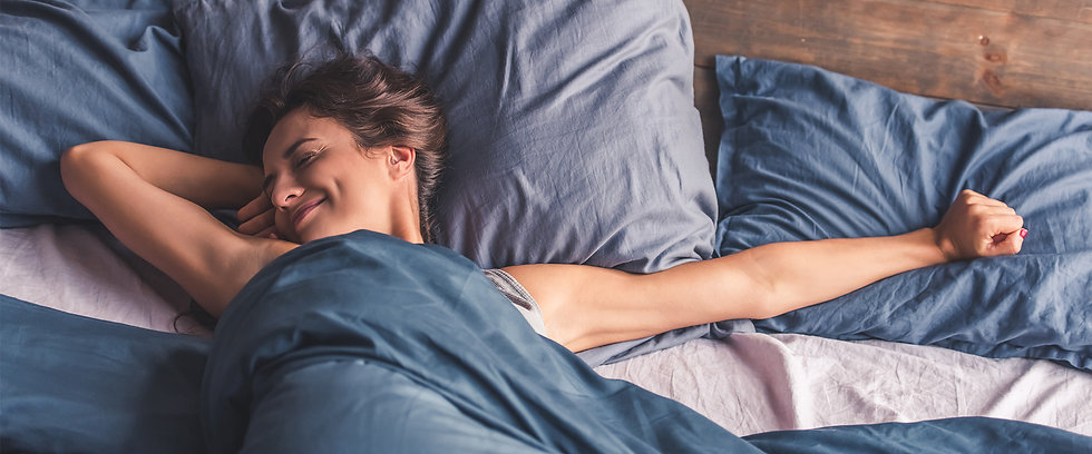 young-woman-waking-up-smiling-stetching.