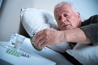 older-man-checking-alarm-clock-in-bed.jp