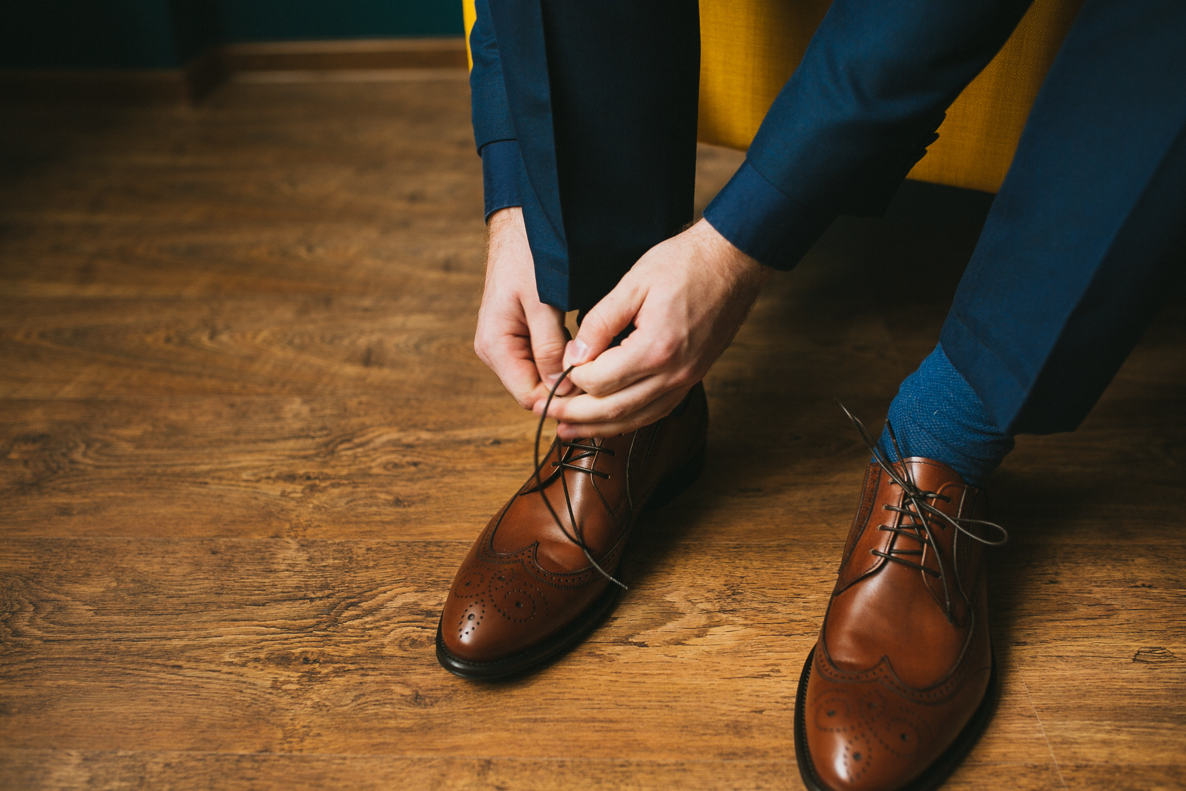 A man in a blue suit ties up shoelaces o