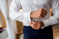 A groom putting on cufflinks as he gets