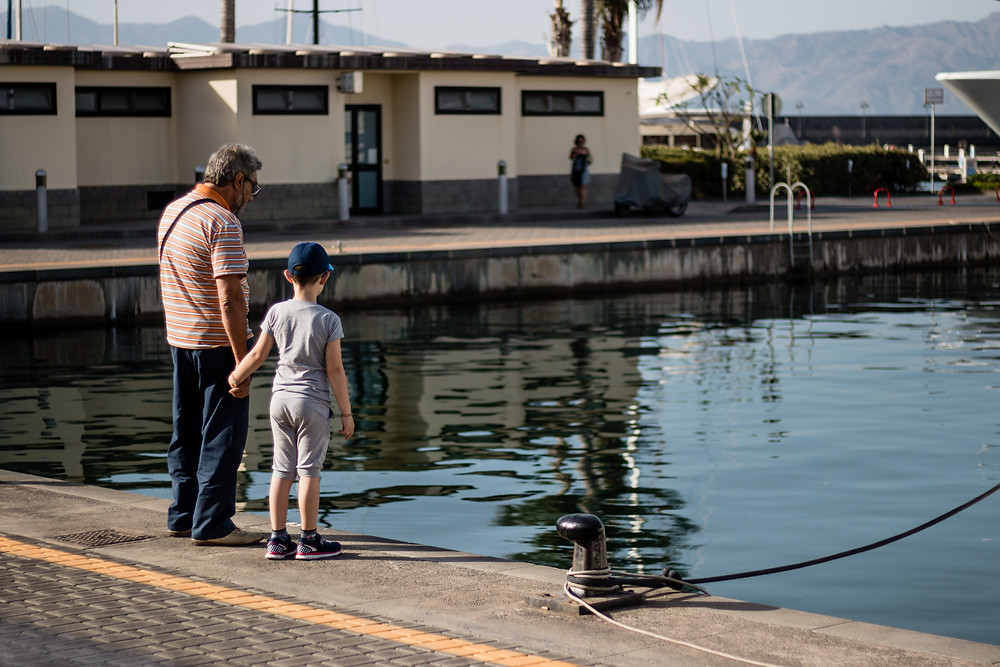Grandfather holding is grandsons hand as they watch the water for fish. Riposto Harbour