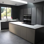 Italian handleless kitchen. A combination of Arredo3 Vulcano glass doors, Comprex brushed aluminium island with 12mm Neolith Cortana marble-style ceramic worktops
