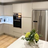 Remo Matt Dove Grey J-profile handleless kitchen with Unistone Carrara Misterio quartz and engineered oak flooring