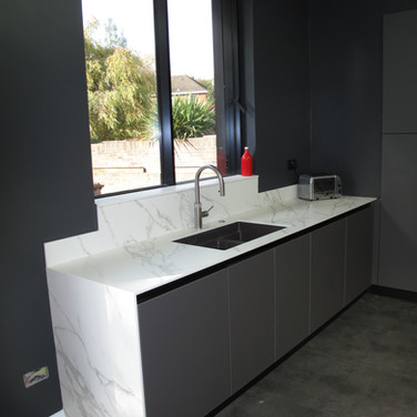 Italian handleless kitchen. This photo clearly shows the Neolith Cortana marble-style ceramic 12mm worktop with Arredo3 Vulcano glass doors