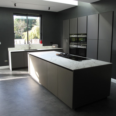 Italian handleless kitchen. A combination of Arredo3 Vulcano glass doors, Comprex brushed aluminium island with 12mm Neolith Cortana marble-style ceramic worktops