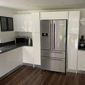 Gloss white true handleless kitchen with American fridge-freezer framed by larder units and top box