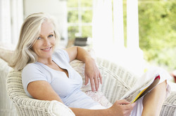 Senior Woman Sitting Outside Reading Magazine