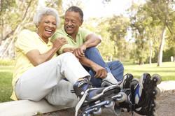 Senior Couple Putting On In Line Skates In Park