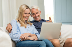 Mature man and his wife working with laptop at home. Senior couple using ecommerce in internet with
