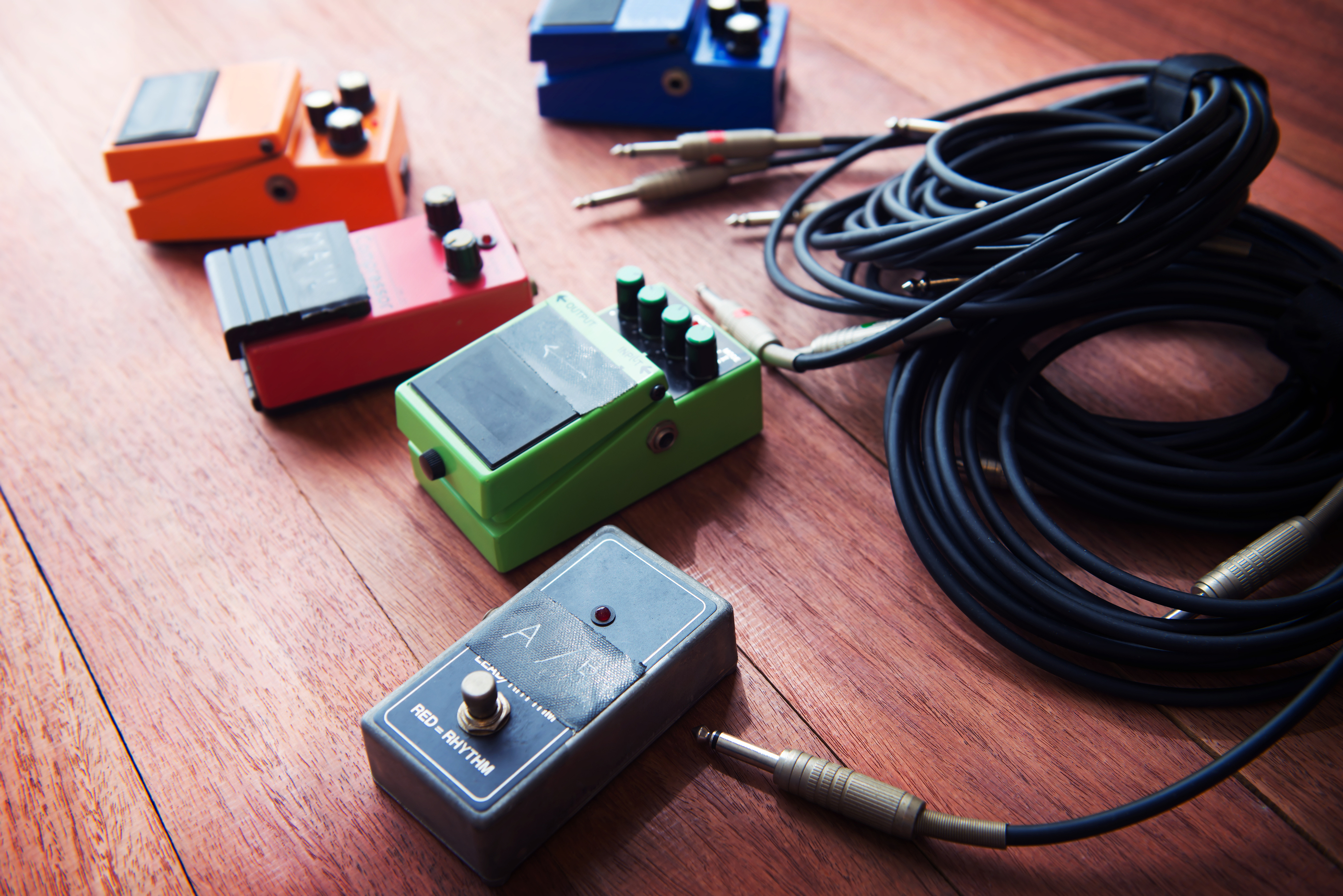 Setting up guitar audio processing effects. Electric guitar stomp box effectors and cables on studio