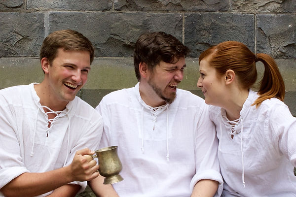 Three actors laughing sharing drinks