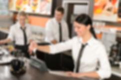 Female cashier giving receipt colleagues