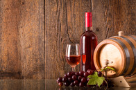 Glass of rose wine with bottle barrel grapes and wooden background