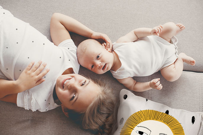 A young girl in a white shirt with black polka dots lays on a couch next to a baby in a white onesie
