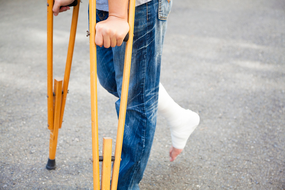 Person with a foot in a cast and crutches.