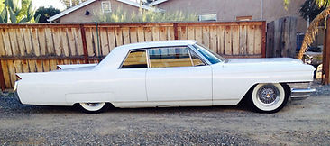 Lowered Cadillac with Brougham 50 wire wheels and wide whitewall tires